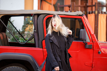 Street fashion concept. Trendy look of stylish young blond woman in black fashion coat and hat. Young lady standing over red car. Sunny spring or autumn weather.