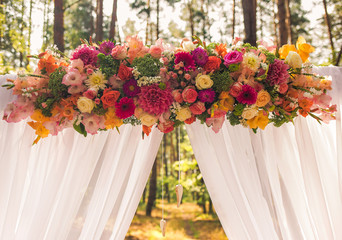 Closeup view of beautiful colorful floral elements of wedding decorations. Settings for romantic wedding ceremony outside at sunny forest. Horizontal color photography.