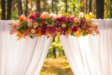 Floral wedding decorations for beautiful romantic wedding ceremony outside at sunny forest. Horizontal color photography.