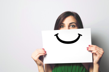 Happy and smiling girl with a smile painted on paper