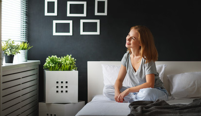 young   woman woke up in the morning in the bedroom by the window with her back