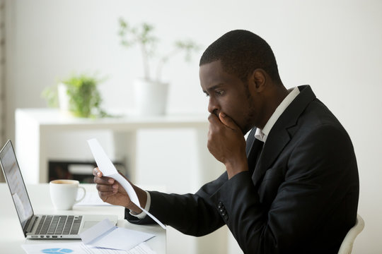 Shocked african-american businessman frustrated by notification about loan debt, confused stunned black employee feeling stressed reading unexpected bad news in letter, got dismissed fired in notice