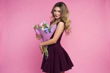Charming, pretty girl is holding a big tulip bouquet in hands. Pink background. Happy woman's day