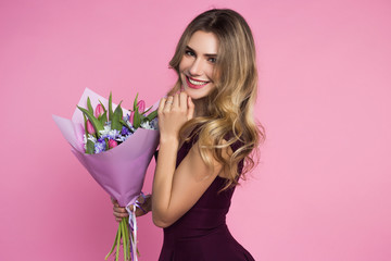 Charming, pretty girl is holding a big tulip bouquet in hands.. Pink background. Happy woman's day