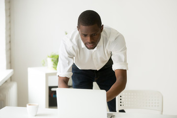 Stressed worried african-american businessman nervous shocked by bad news online or scared of negative message, frustrated black entrepreneur looking at laptop screen confused by computer error