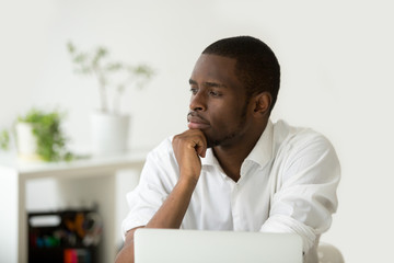 Young african-american thoughtful businessman holding hand on chin planning future project at work with laptop, black meditative african entrepreneur thinking of new idea for business improvement