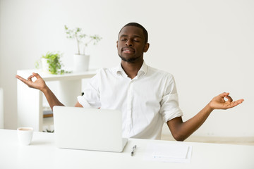 Calm happy african american man meditating at home office desk with laptop developing focus and concentration, black employee practicing yoga at work, no stress free, positive thinking, peace of mind