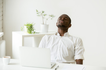 African office worker relaxing with eyes closed sitting at work desk with laptop, black employee taking rest doing exercise for relaxation at workplace during break, meditating or breathing fresh air