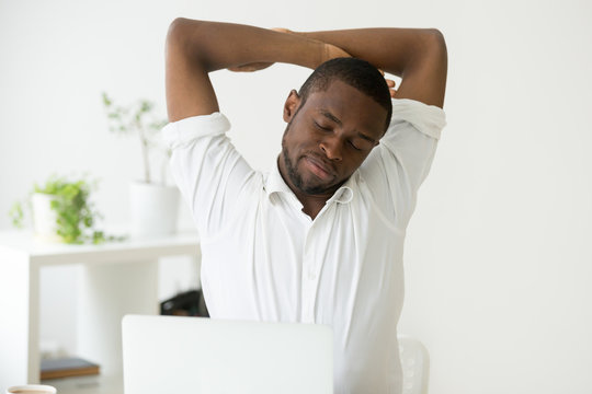 African american man stretching doing easy office exercises to relieve muscle tension from sedentary work, young black employee taking break for relaxation at workplace, computer syndrome prevention