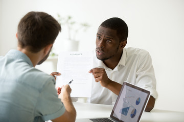 Disgruntled angry african businessman arguing disagreeing about business contract loan fraud, dissatisfied black investor having dispute with white partner pointing at document breaking agreement