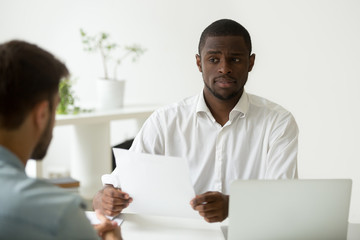 African american hr manager looking doubtful about hiring incompetent candidate, uncertain distrustful black employer skeptical about applicant cv, bad resume failed job interview performance concept