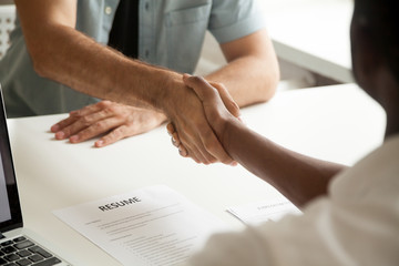 Employment handshake or making good first impression at successful interview concept, african employer and caucasian employee shake hands, black recruiter welcoming new white job candidate, close up