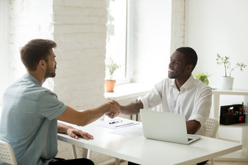 African and caucasian businessmen shaking hands over office desk, satisfied white partner closing successful business deal with black investor, handshake after making agreement or getting hired
