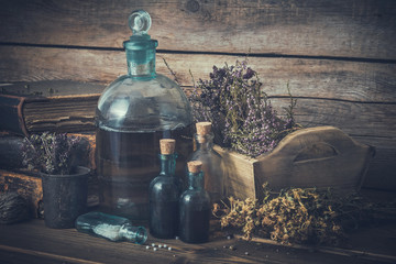 Tincture bottles, vial of homeopathy globules, old books, dry healthy herbs and curative drugs. Herbal and homeopathic medicine. Retro styled.