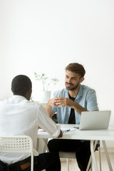 Two diverse young businessmen talking discussing new project idea, caucasian hr holding job interview with african candidate, multiracial colleagues working together in office teamwork, vertical view