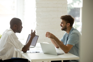 Diverse friendly multiracial colleagues discussing new interesting idea talking at workplace, african american and caucasian businessmen laughing having fun pleasant conversation at work in office