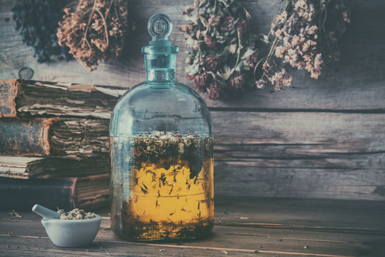 Tincture or potion bottle, old books, mortar and hanging bunches of dry healthy herbs. Herbal medicine. Retro styled.