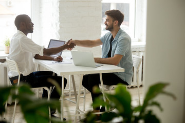 Black and white entrepreneurs shaking hands sitting at office desk, satisfied multi-ethnic casual businessmen binding business deal with handshake, thanking for help support in successful teamwork