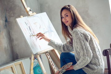 Young woman artist painting at home creative painting picture