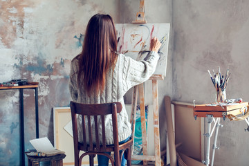 Young woman artist painting at home creative person