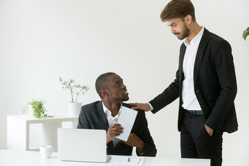 Happy thankful african american office worker receiving envelope with reward money bonus from caucasian boss appreciating good work results, employee promotion, motivation and recognition concept