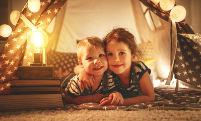 happy family children brother and sister play, laugh and hug   in dark tent in playroom