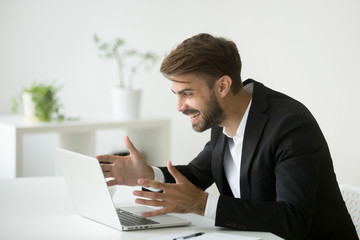 Happy surprised businessman in suit looking at laptop screen excited by online project result, successful entrepreneur sitting at office desk celebrating good news in email, motivated by business win