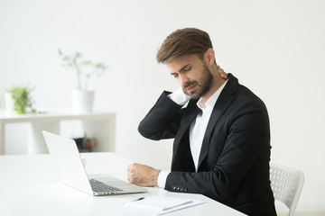 Young businessman in suit feels neck pain massaging tensed muscles after sedentary work sitting on...