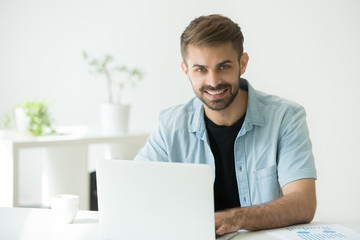 Smiling businessman working with statistics and laptop in office, friendly entrepreneur freelancer looking at camera at workplace, happy intern or marketing seo manager using computer, portrait