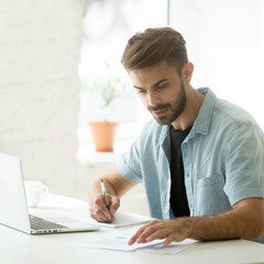 Focused marketing manager analyzing statistical business result working on report making notes, serious casual young businessman doing stats data analysis sitting at workplace in office with laptop