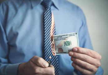Businessman burning hundred dollar.