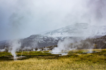 Steam Rising from the Strokkur Geysir Field with Mountains in the Background