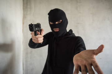 Masked robber with gun aiming into people