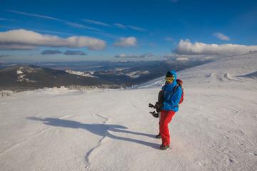 Snowboarder posing on a mountain ridge