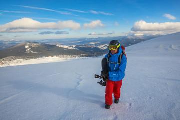 Snowboarder climbs on a mountain ridge