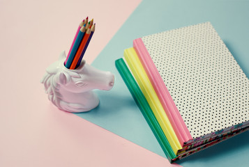 stationery items pop art pastel background unicorn pencil holder and note-books