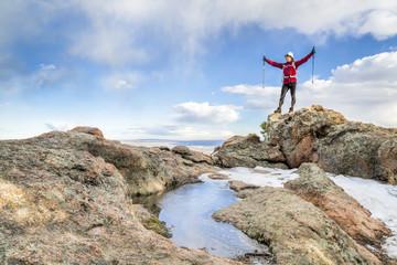 hiker enjoying reaching mountain top