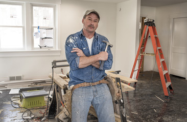 Male carpenter wearing leather tool belt and holding hammer leaning against saw horse work table with chop saw in home remodel