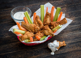 chicken wings with celery and carrot sticks in basket with side dip
