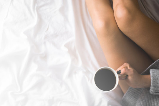 A cup of coffee in their hands in bed on a white blanket, simple, home, space in the frame copy space top view White light tinting