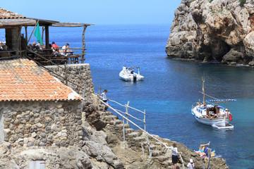 Europe, Spain, Balearic Islands, Mallorca. Cala Banyalbufar. Beachfront swimming. Harbor, Sunbathers. Boats.