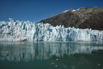 crisp reflection of Margerie glacier in clear ocean water in Glacier Bay National Park on a luminous summer day