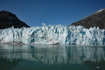 Margerie glacier reflecting in clear ocean water in Glacier Bay National Park on a sunny summer day