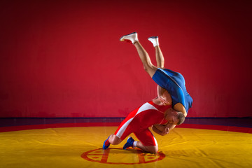 Two strong wrestlers in blue and red wrestling tights  making a hip throw  on a yellow wrestling carpet in the gym. Young man doing grapple.