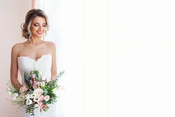 Portrait of a beautiful bride with a wedding bouquet. Blonde girl with curly hair and fashion makeup. Wall mural