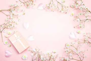 Frame of gypsophila flowers and gift box on pink background. Space for text.