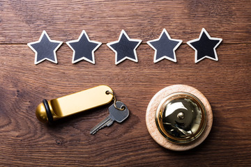 Five Stars, Service Bell And Hotel Key On Wooden Desk