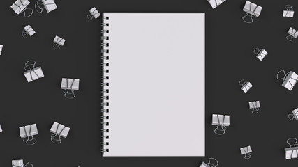 Blank spiral notebook with white binder clips on black table
