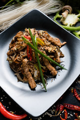rice noodle pork and vegetable on a plate. traditional asian cuisine food preparing craft
