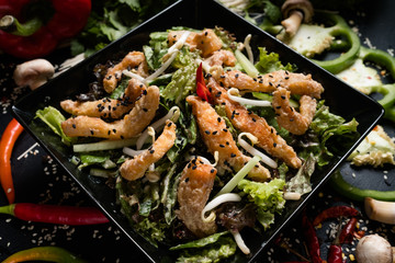 fried squid wheat sprouts and vegetable salad in a bowl on dark background. oriental cuisine food. traditional meal.
